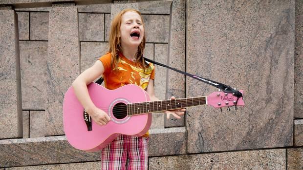 Mächen mit Guitarre singt auf der Straße