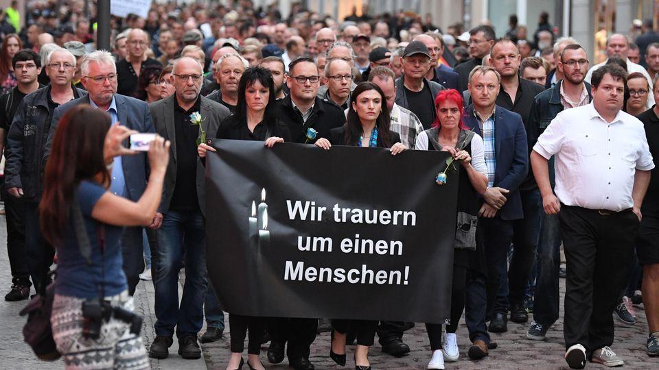 Hunderte Teilnehmer eines Trauermarschesfür den verstorbenen 22-Jährigen ziehen durch Köthen