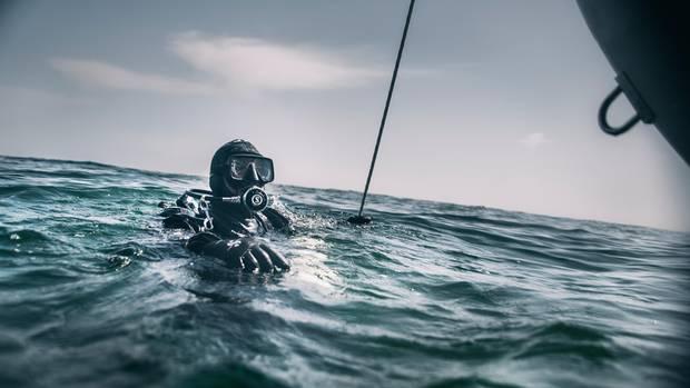 Schatztaucher Andi taucht gerade neben dem Schlauchboot aus der Nordsee auf.