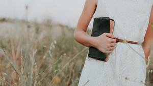 Frau mit Bibel in Feld