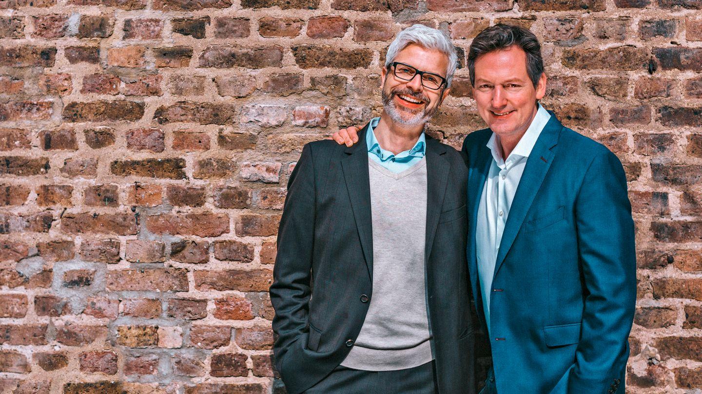 Eckart von Hirschhausen und Tobias Esch stehen vor einer Backsteinwand