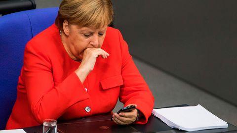 Angela Merkel trägt während der Generaldebatte einen roten Blazer und guckt auf ihr Handy