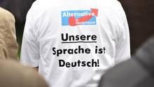 """Ein Anhänger der AfD mit dem Aufdruck """"Unsere Sprache ist Deutsch!"""" sitzt während der Rede des Parteivorsitzenden Meuthen beim politischen Frühschoppen auf dem Volksfest Gillamoos auf einer Bank"""