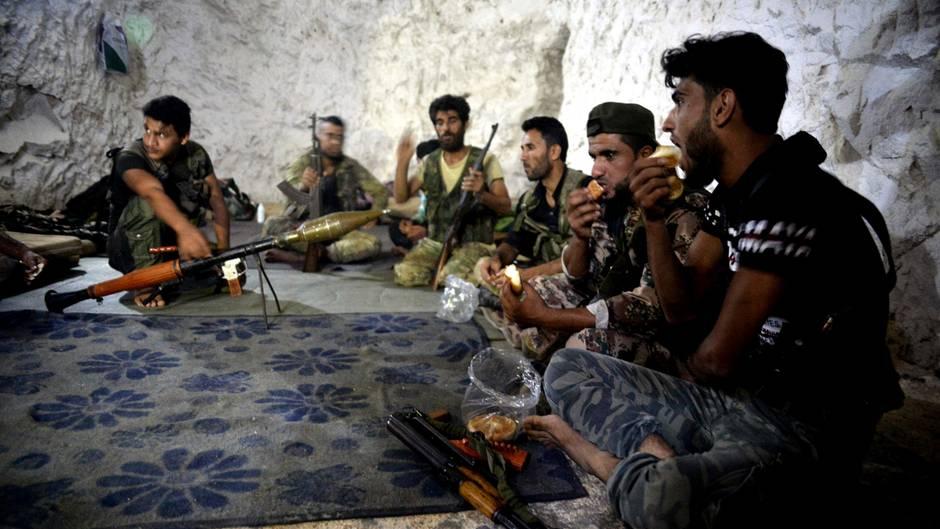 Syrien, Idlib: Kämpfer und Soldaten der Freien Syrischen Armee sitzen in einer Höhle.