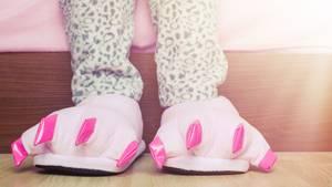 Kinderbeine mit Schlafanzug und Dino-Hausschuhen
