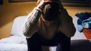 Eine niedergeschlagene Frau sitzt auf dem Bett