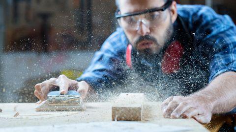 Ein Tischler schleift eine Holzplatte ab