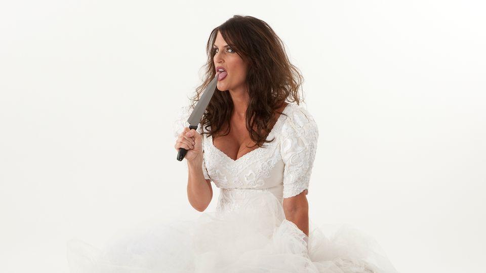 Frau in Brautkleid mit Messer