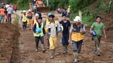 Freiweillige Helfer gehen in Gummistiefeln und mit geschulterten Schaufeln zum Ort eines Landrutsches