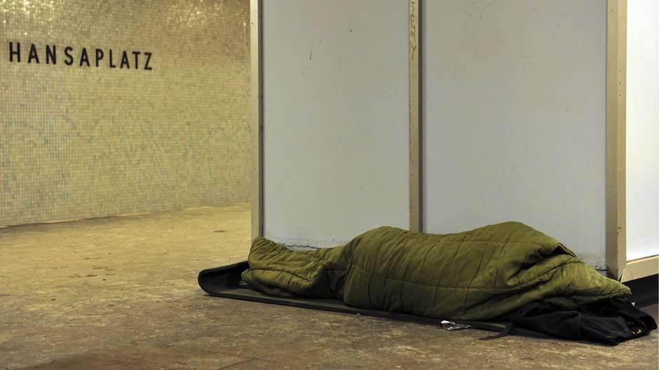 Ein Obdachloser schläft auf einem U-Bahnsteig in Berlin