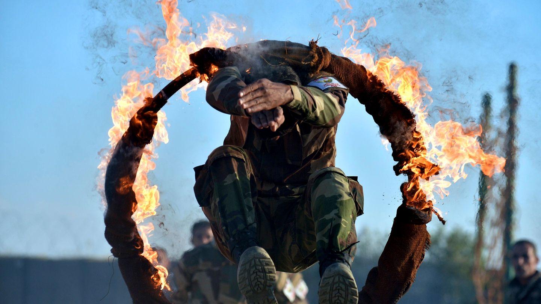 Mann springt durch brennenden Reifen