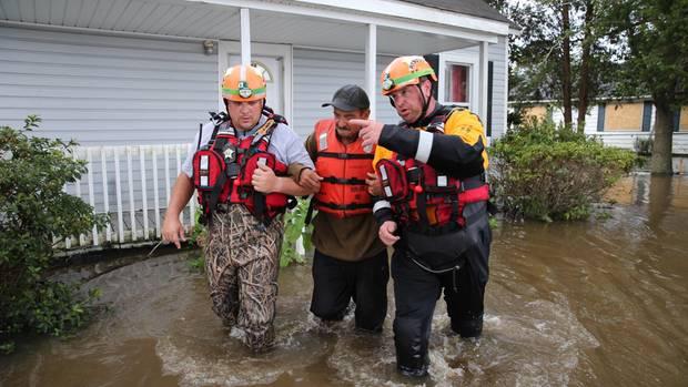 """Helfer evakuieren einen Anwohner in North Carolina aus seinem durch Hurrikan """"Florence"""" überschwemmten Haus"""
