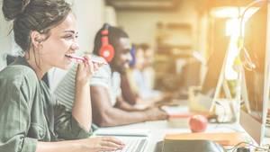 Eine junge Frau sitzt lächelnd am Computer und hält sich mit der linken Hand einen Kugelschreiber an den Mund