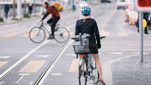Eine Fahrradfahrerin hält im Straßenverkehr an einer Kreuzung