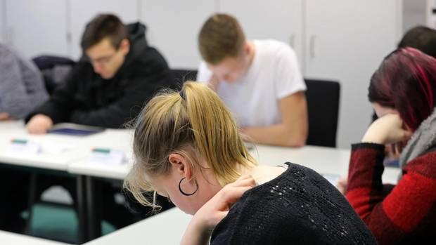 Zwei junge Frauen und zwei junge Männer sitzen über ihrer Theorieprüfung für den Führerschein gebeugt