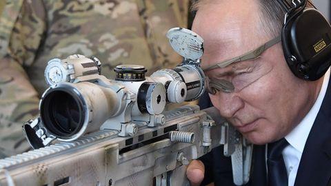 Der russische Präsident Wladimir Putin schießt mit einer neuen Kalaschnikow auf einem Geländer des Waffenherstellers