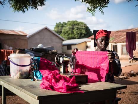 """Humu Mohamad, 23    """"Ich hatte schon Geld gespart, war fest entschlossen zum Trip nach Europa. Von den Gefahren wusste ich: Als Frau hätte ich unterwegs vergewaltigt werden können. Aber hier in Tamale hatte ich einfach keine Hoffnung mehr. Aminu Munkaila hat mich überzeugt zu bleiben. Seine Organisation AFDOM finanzierte mir eine zweijährige Ausbildung zur Schneiderin und dann eine eigene Nähmaschine. Nur mit Handantrieb, aber egal. Ich arbeite im Freien, im Schatten eines Baums, da gibt es eh keinen Strom. Für eine Werkstatt fehlt mir noch das Geld. Aber ich habe genug Kundschaft."""