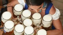 Eine weibliche Bedienung im Dirndl trägt zehn Masskrüge auf dem Oktoberfest
