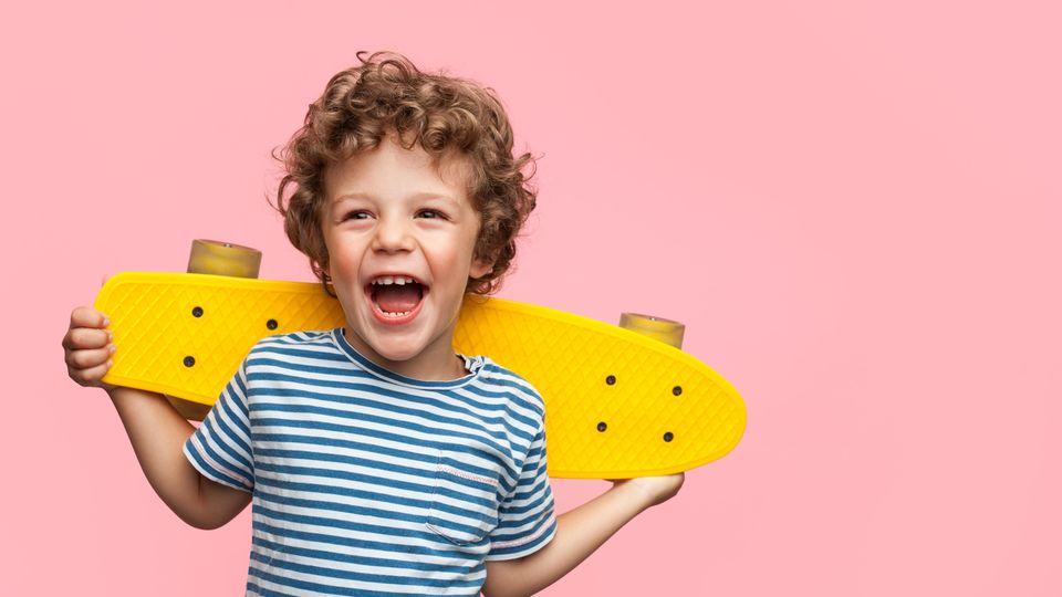 Ein Junge mit braunen Locken und geringeltem T-Shirt lacht und hält dabei ein gelbes Skateboard hinter dem Rücken