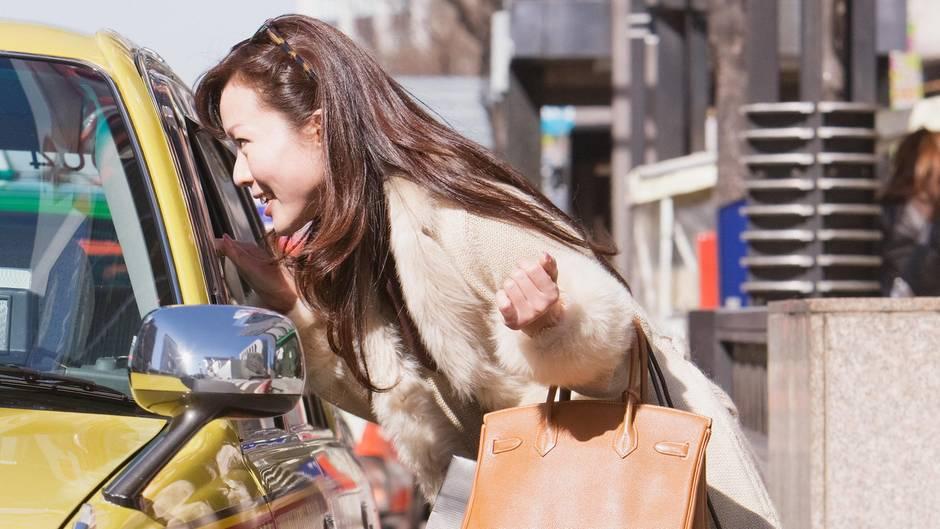 Eine Frau fragt einen Taxifahrer nach dem Weg
