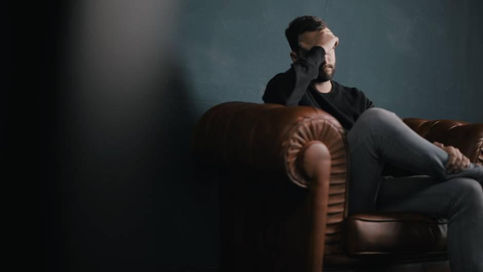 Mann sitzt im Sessel und denkt nach