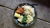 Auf einem Tellermit einem Bananenblatt als Unterlage serviert: Im Dorf Yorkin werden neben Reis auch ein Stück Hühnerfleisch sowie gekochte Maniok-Knolle aufgetischt.
