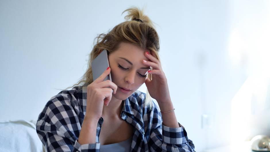 Eine Frau telefoniert und fasst sich dabei an den Kopf
