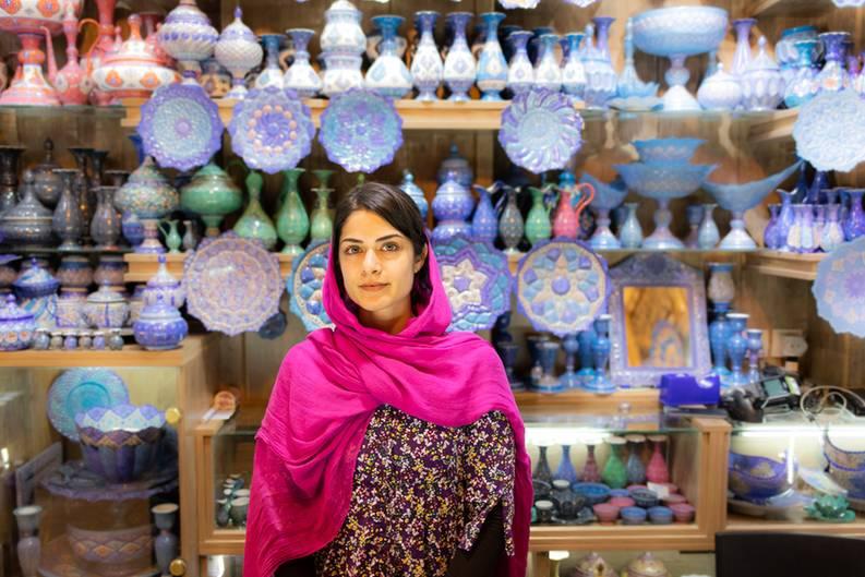 """""""Eine junge Frau arbeitet als Verkäuferin in einem Geschäft in Shiraz. Beim Vorbeilaufen hat mir sofort der Farbkontrast zwischen ihrer Kleidung und der Waren im Hintergrund gefallen und ich habe sie gefragt, ob ich sie fotografieren darf."""""""