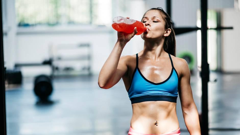 Eine Frau trinkt eine Schorle nach dem Sport