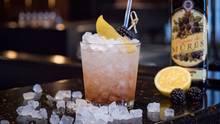Ein Gin-Drink mit Brombeeren steht auf einem Tresen
