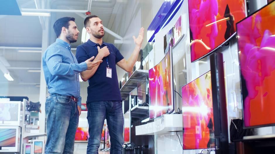 Ein Kunde lässt sich beim Fernseher-Kauf beraten