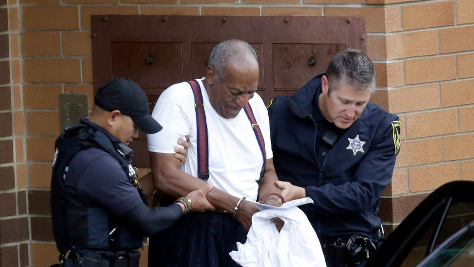 Bill Cosby wird in Handschellen von zwei Polizisten eine Treppe heruntergeführt. Ein dunkler Wagen steht am Fuß der Treppe