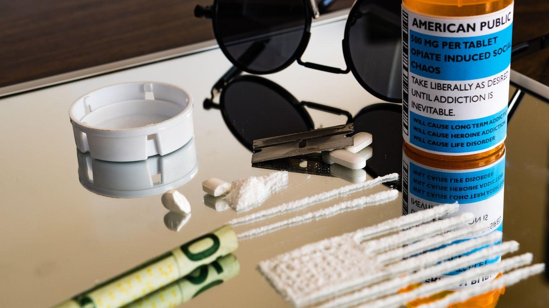 Zerstoßene Tabletten und ein gerollter Geldschein liegen auf einem Spiegel