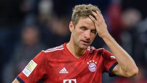 Thomas Müller steht im roten Dress des FC Bayern München auf dem Platz fasst sich mit der linken Hand an den Kopf