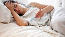 Eine Frau liegt mit Schüttelfrost und Fieber im Bett