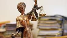 Eine kleine goldene Statue der Justizia steht vor einem Haufen Akten