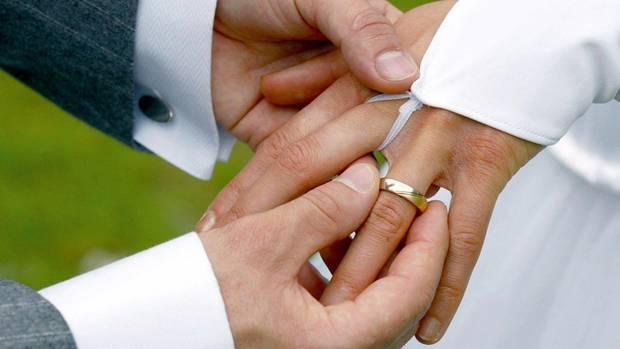 Ein steckt seiner Frau bei der Hochzeit den Ring an den Finger