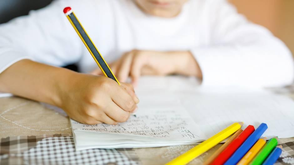 Ein Kind schreibt mit einem Bleistift in ein Schreibheft