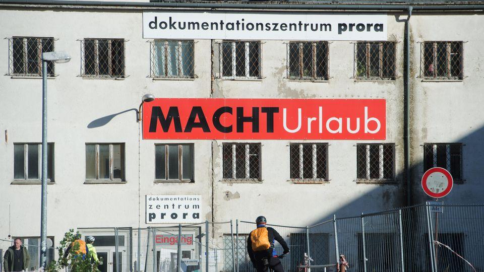 """Ein Schild mit der Aufschrift """"MACHT Urlaub"""" hängt an der Fassade des Dokumentationszentrums Prora"""