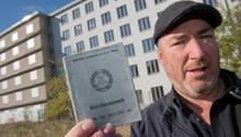 Christian Schmidt, ehemaliger DDR-Bausoldat, zeigt vor Block 5 in Prora seinen ehemaligen Wehrdienstausweis