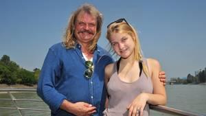 Der Musiker Leslie Mandoki steht an der Rehling eines Schiffes auf einem Fluss, neben sich seine blonde Tochter Julia