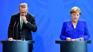 Recep Tayyip Erdogan steht links und schaut auf das Rednerpult vor sich, während Angela Merkel rechts am Pult steht und spricht