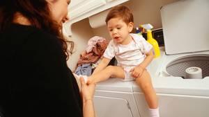 Eine Mutter zieht ihrem Sohn Socken an