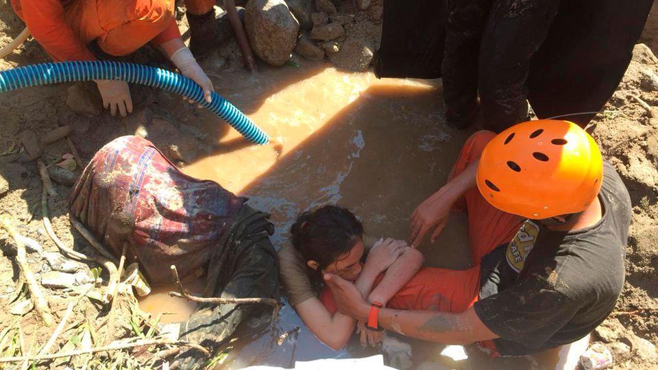 Helfer retten eine Frau nach den schweren Beben und dem Tsunami in Indonesien