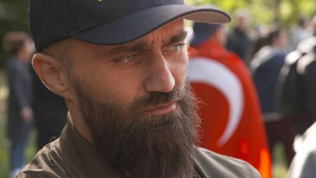 Ünsal Arik (37) beobachtet die Moschee-Eröffnung in Köln durchRecep Tayyip Erdogan im Hintergrund.