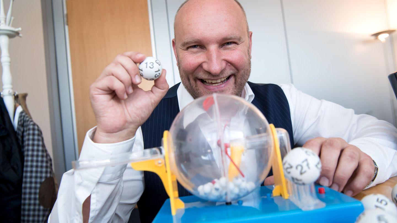 Rainer Holmer, Gewinnbetreuer von Lotto Bayern, sitzt in seinem Büro an einem Spielzeug-Ziehungsgerät für Lottokugeln