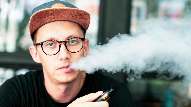 Ein Mann sitzt in einem Straßencafé und zieht an einer E-Zigarette