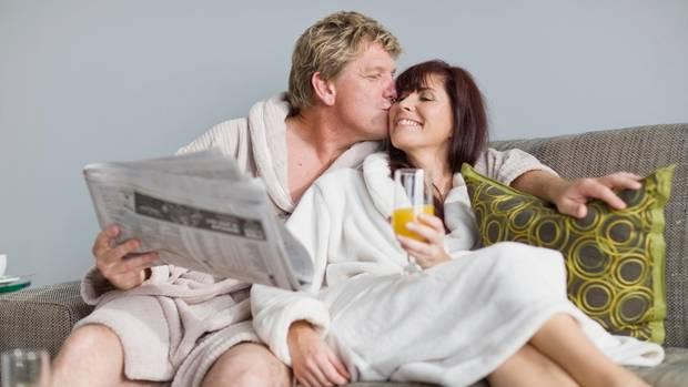 Ein Paar sitzt im Bademantel auf dem Sofa und freut sich