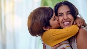 Ein kleiner Junge küsst seine Mutter auf die Wange