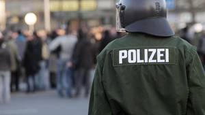 Ein Polizist steht vor einer Menschenmenge